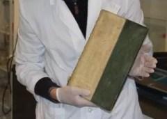 Un investigador sostiene (cuidadosamente) uno de los libros envenenados con arsénico. El tomo data del Renacimiento, pero es probable que haya sido cubierto con pintura de arsénico por los equivocados victorianos.