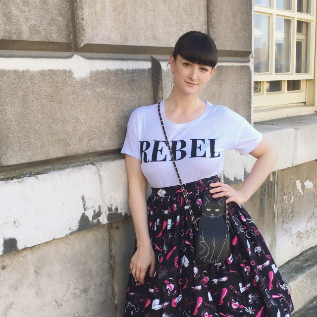 Cropped image of Caz leaning against a wall in skirt and t-shirt © Quirk and Folly