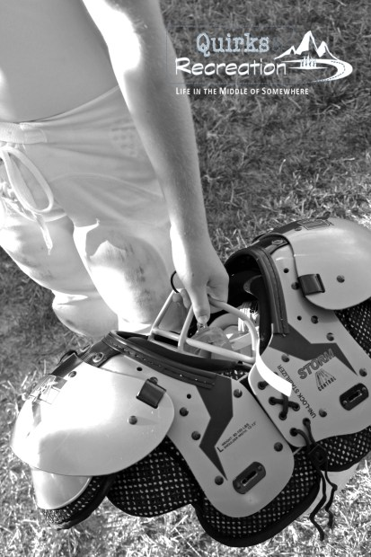 black and white photo of boy holidng football pads, helmet