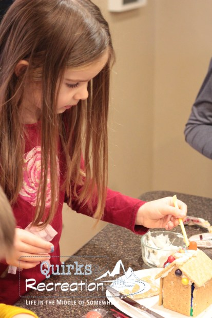 girl decorating a gingerbread house with candy