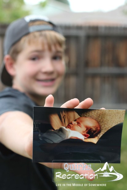 teenage boy holding a photo of himself as a baby