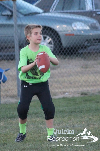 boy playing quarterback in a flag football game