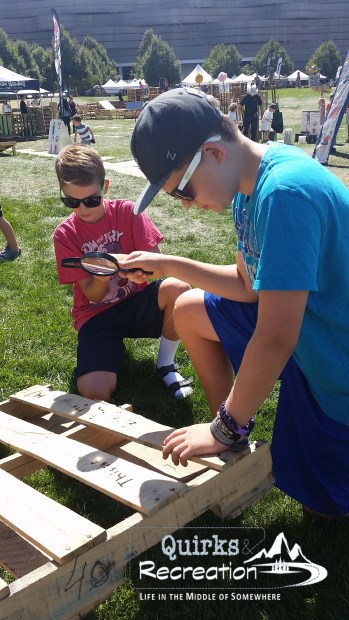boys using magnifying glasses to burn a wood pallet