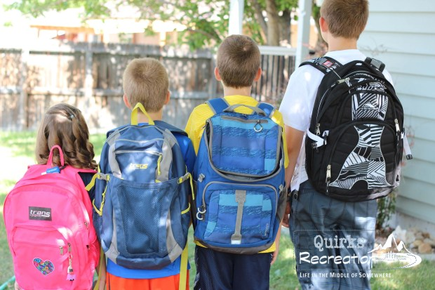 Siblings showing their school backpacks