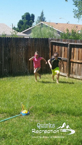 two siblings running through a backyard sprinkler