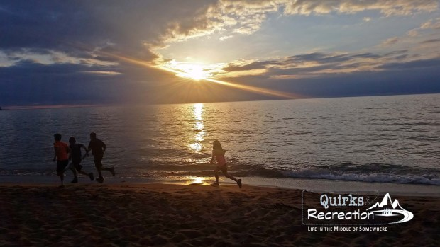 children running on the shore of Lake Superior at sunset