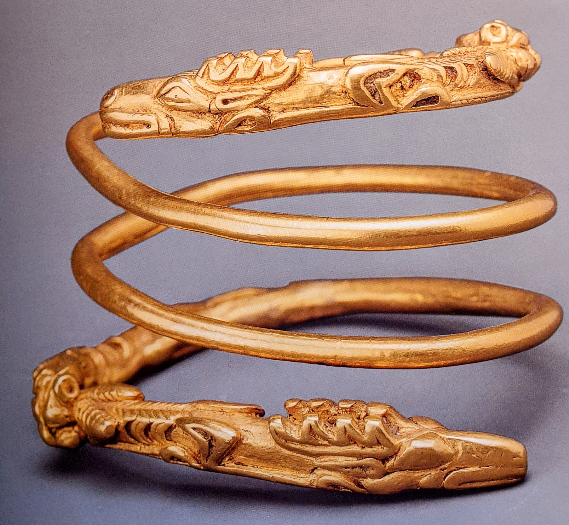 Spiral gold bracelet with cat attacking stag terminals