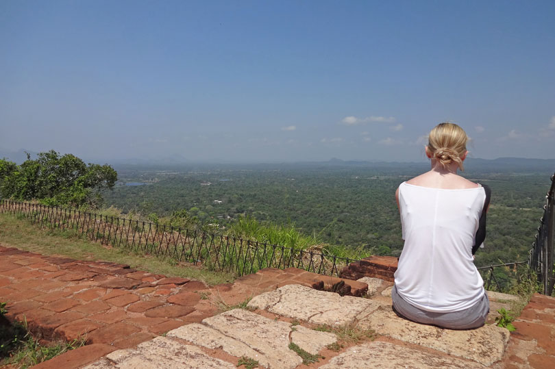 Blonde haired girl admiring the view from the top of Sigiriya in Sri Lanka