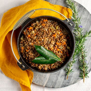 A cast iron pot of lentils, sitting on a marble chopping board with an orange linen napkin alongside. Inside the pot there are cooked lentils with small chunks of celery and carrot, and two bay leaves sitting on top.