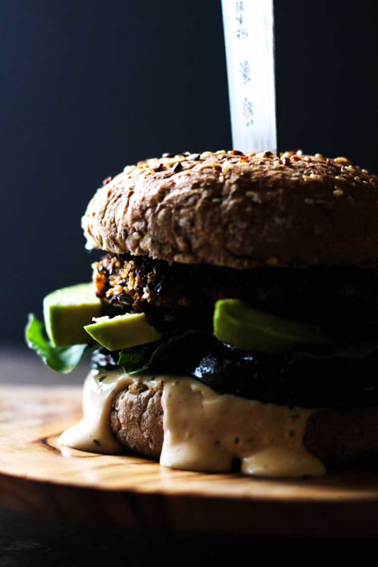 Close up side view of a black bean burger, assembled with avocado, mayo and rocket.