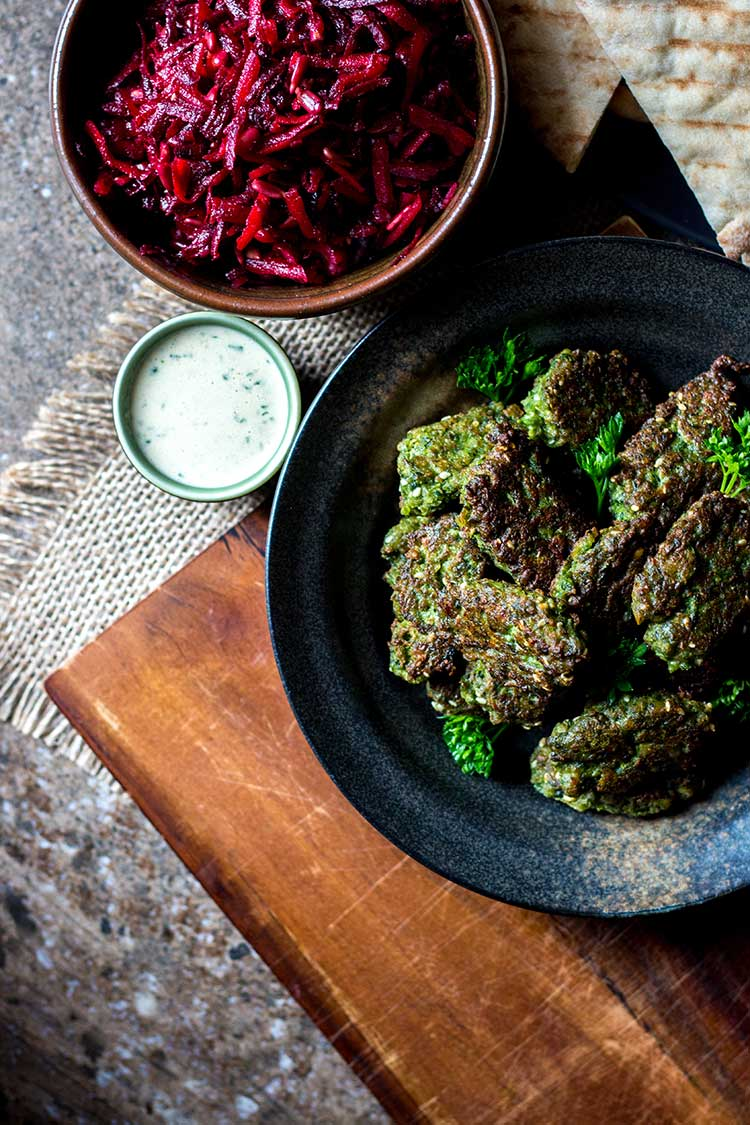 Overhead photo of broad bean falafel, tahini sauce and beetroot slaw, ready to serve with pita pockets.