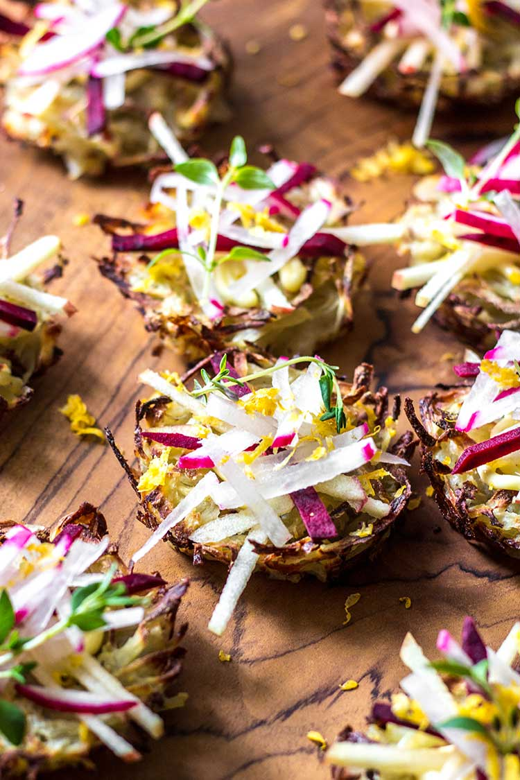 Overhead shot of baked potato nests, topped with aioli, and matchsticks of radish, apple and beetroot (vegan and gluten free).
