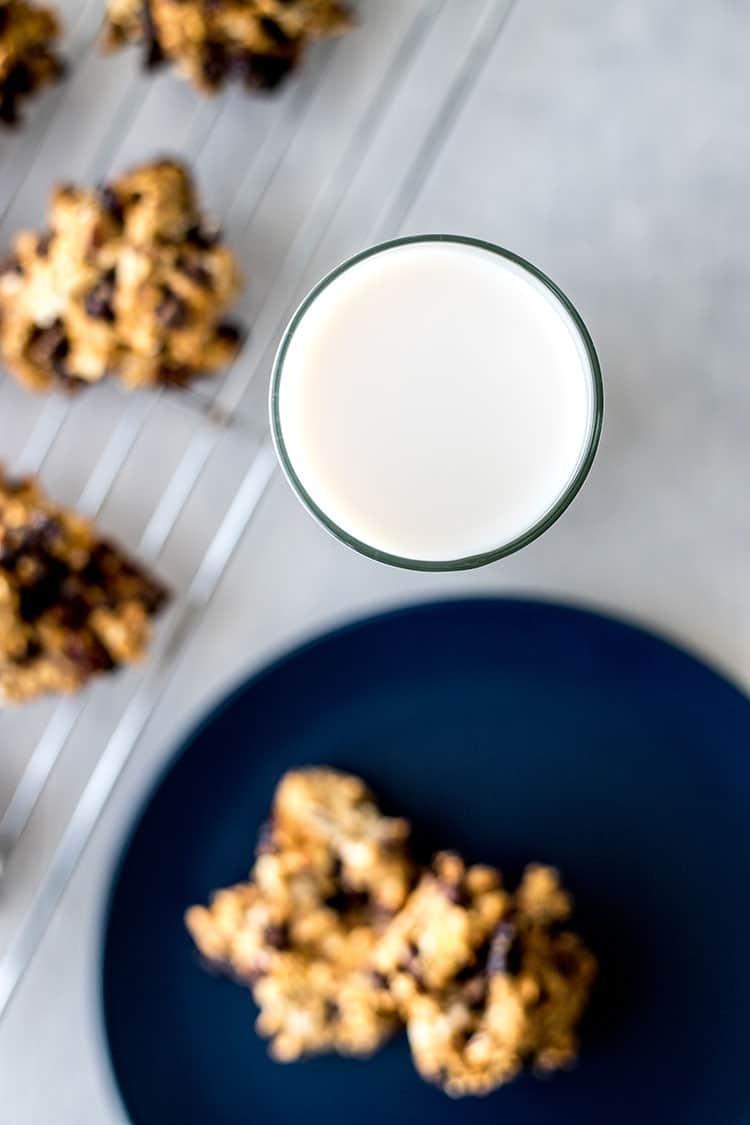Gluten-free vegan cookies on a baking rack, alongside a glass of almond milk.