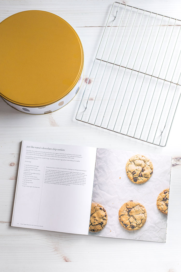 Picture of an open cookbook, cookie tin and cooling rack.