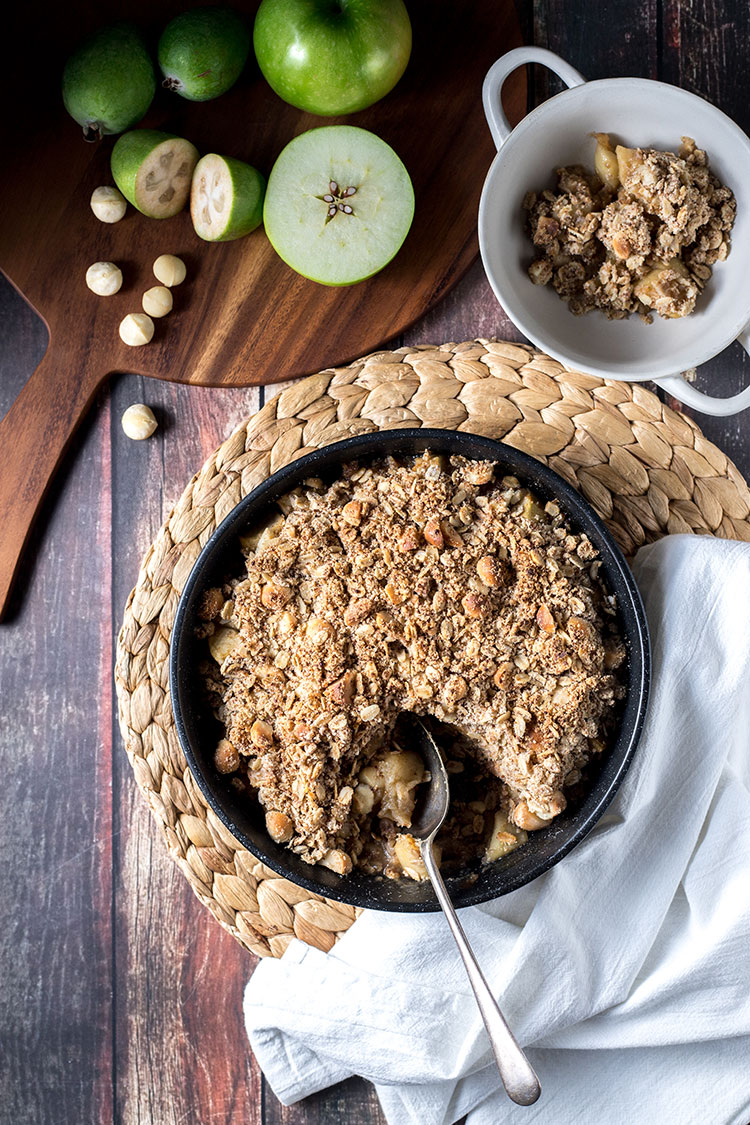 Apple and feijoa crumble with macadamias, pictured being served on a tabletop.