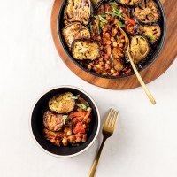 Maghmour - Lebanese eggplant and chickpea stew in a casserole dish, sitting on a wooden board ready to be served.