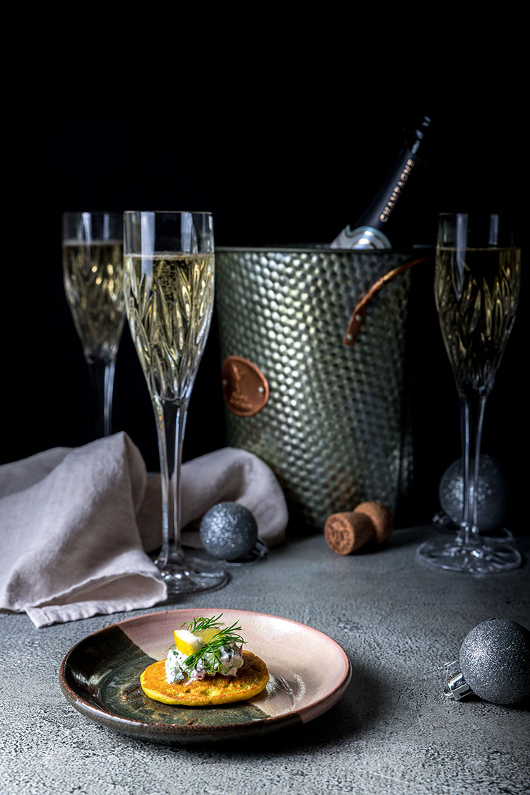A vegan blini on a small side plate, with champagne flutes, a champagne bucket and bottle of champagne in the background.