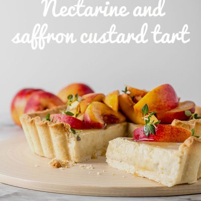 A vegan custard tart sitting on a chopping board, with a slice removed. The tart is topped with sliced nectarines, drizzled with honey and sprinkled with fresh thyme leaves.