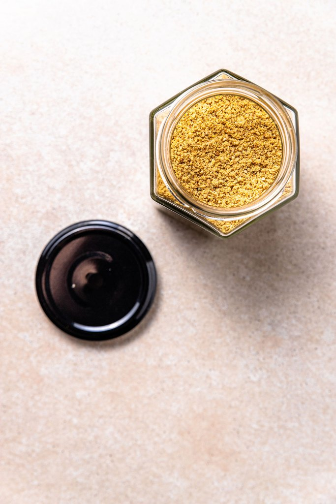 A hexagonal shaped jar full of golden coloured vegan parmesan sprinkle. The jar is open with the lid sitting beside it.