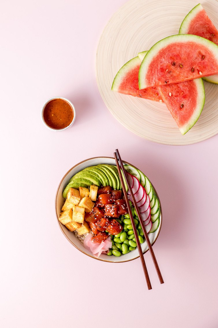 Overhead shot of a watermelon poke bowl (a bowl with edamame beans, sliced radish, cucumber and avocado, fried tofu and marinated watermelon visible), sliced watermelon on a chopping board, and a small dish of watermelon poke marinade.
