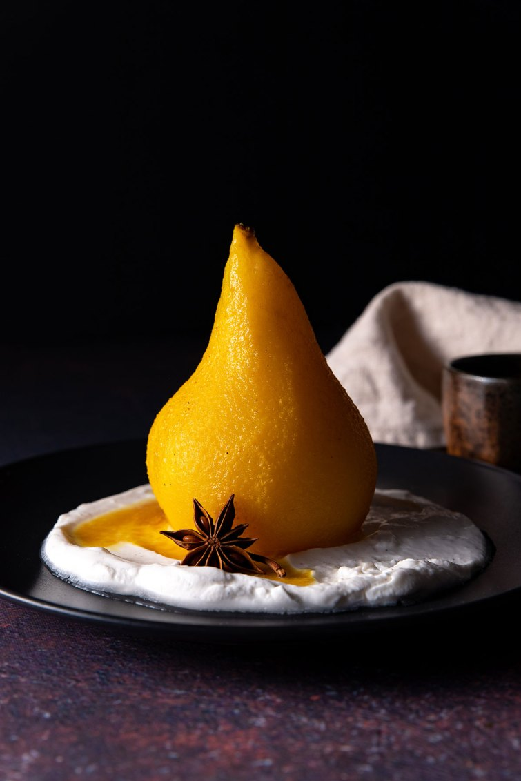 A close up picture of a whole, golden coloured poached pear sitting on a black plate, with coconut yoghurt, a drizzle of poaching liquid, and a star anise.
