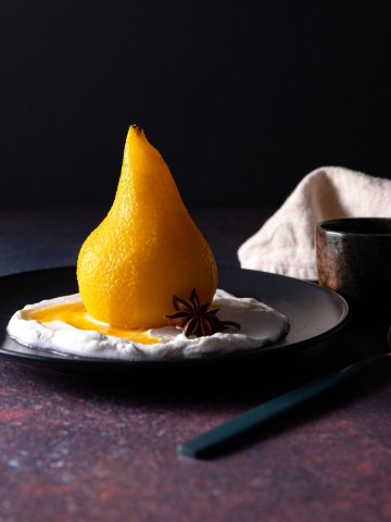A whole, golden coloured poached pear sitting on a black plate, with coconut yoghurt and a star anise.