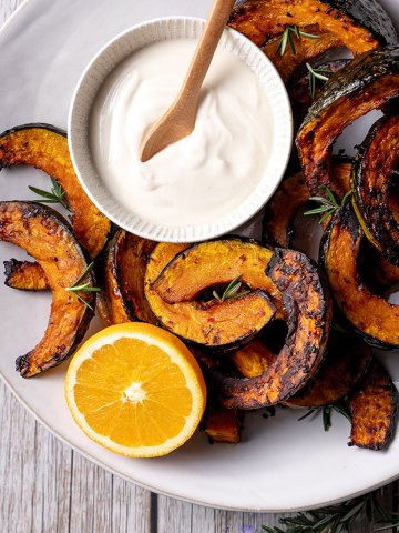 A white plate with slices of roast buttercup pumpkin, pictured with a small bowl of coconut yoghurt and tahini sauce, half an orange and some small sprigs of rosemary.