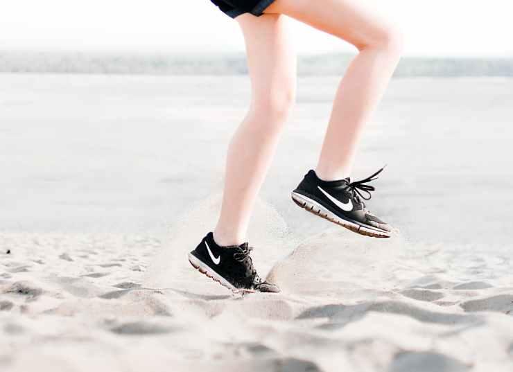 photo of woman wearing pair of black nike running shoes