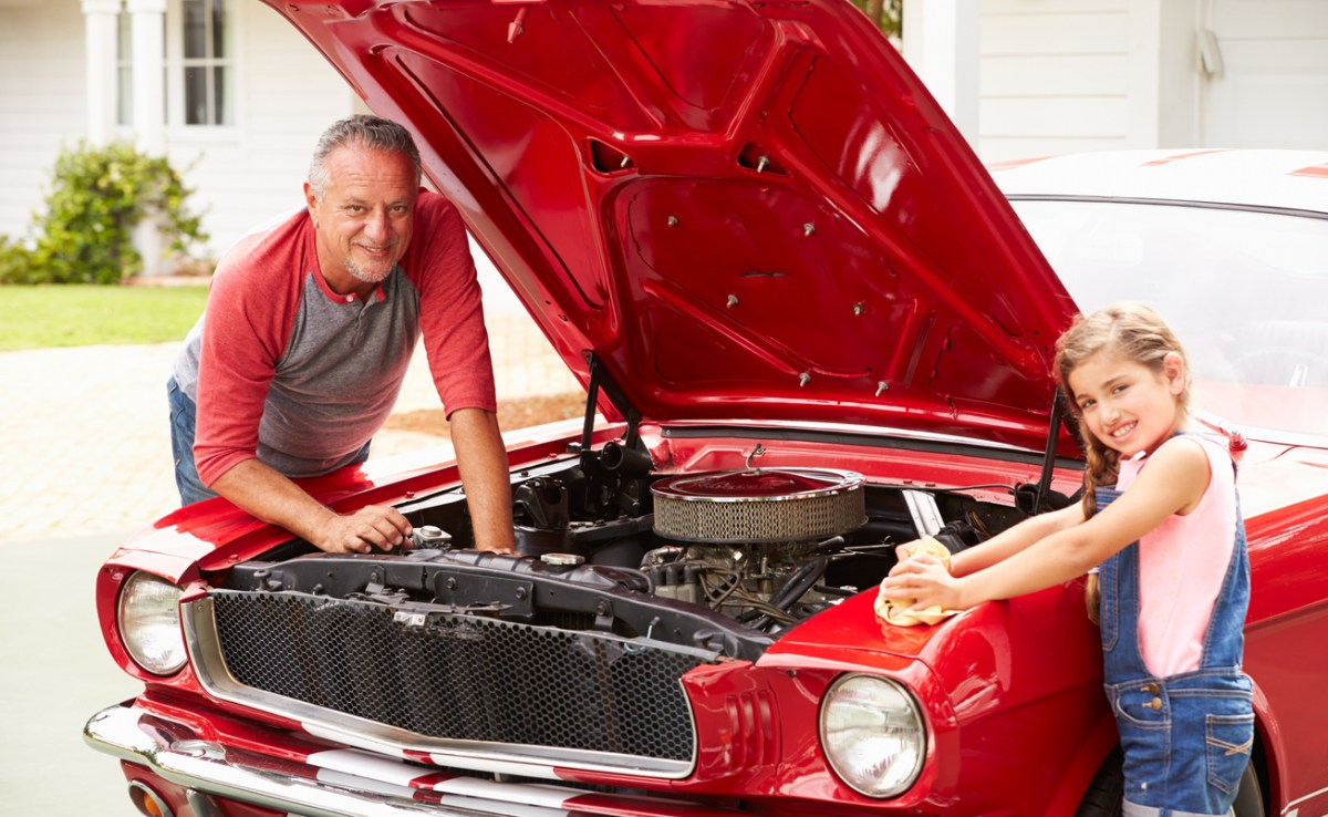 Grandfather And Granddaughter Working On Classic Car Smiling To Camera