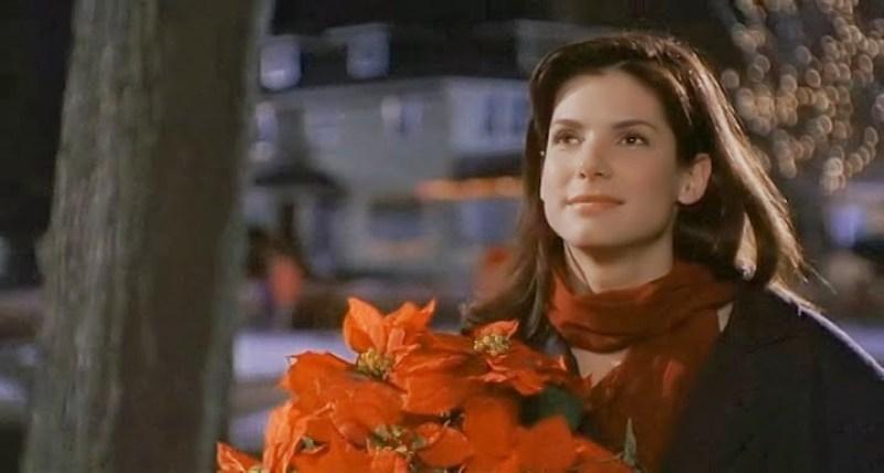 Sandra Bullock em uma cena do filme Enquanto voce dormia segurando flores na mão