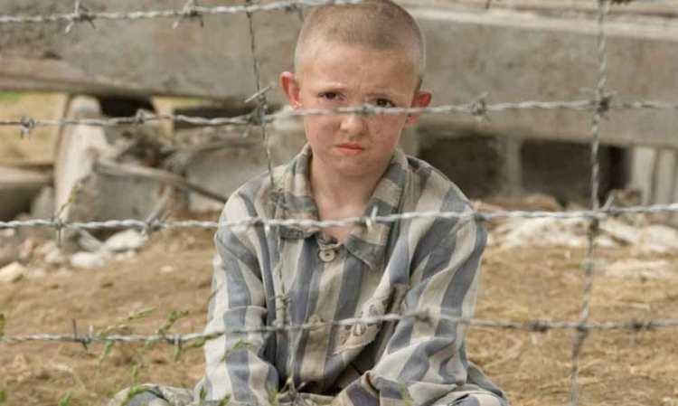 menino do pijama listrado dentro do campo de concentração conversando com outro menino
