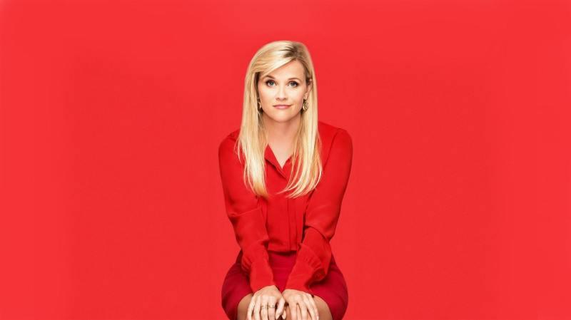 atriz sentada em uma cadeira vestida de vermelho e atrás uma parede vermelha também