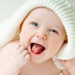 bebe menina vestida de branco deitada na cama sorrindo