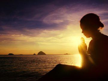 mulher orando sob o nascer do sol