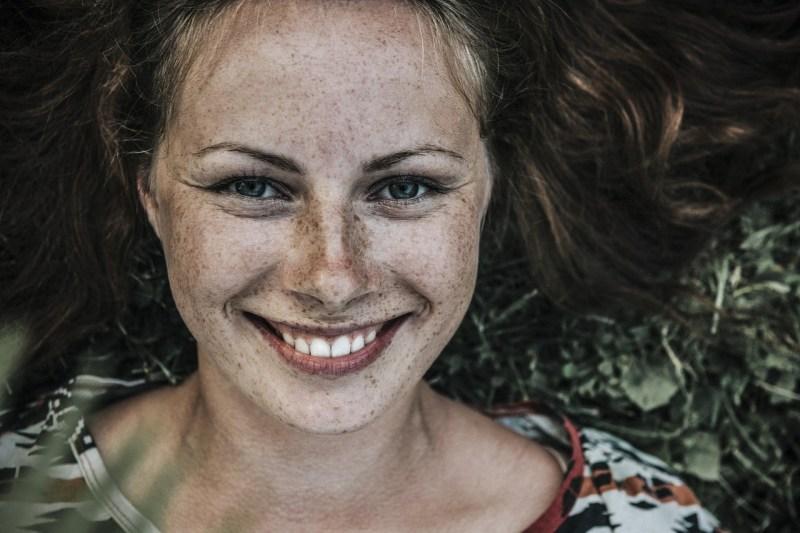 foto de uma mulher ruiva bonita com sardas sorrindo e deitada em um gramado