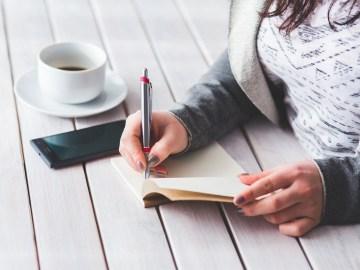 mulher escrevendo fazendo prova e tomando um café