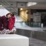 mulher dormindo em público cansada em um banco