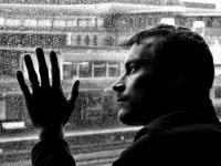 homem triste e depressivo na janela de sua casa
