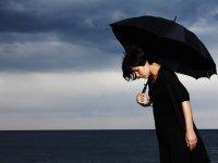 mulher com um guarda-chuva na mão olhando para o chão