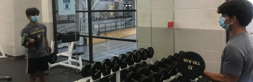 QU student works out with dumbbells while wearing a mask.