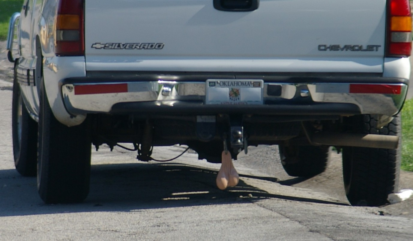 A photograph of the rear end of a pickup truck bumper, with fake rubber bull testicles hanging from the tow hitch.  Seriously.