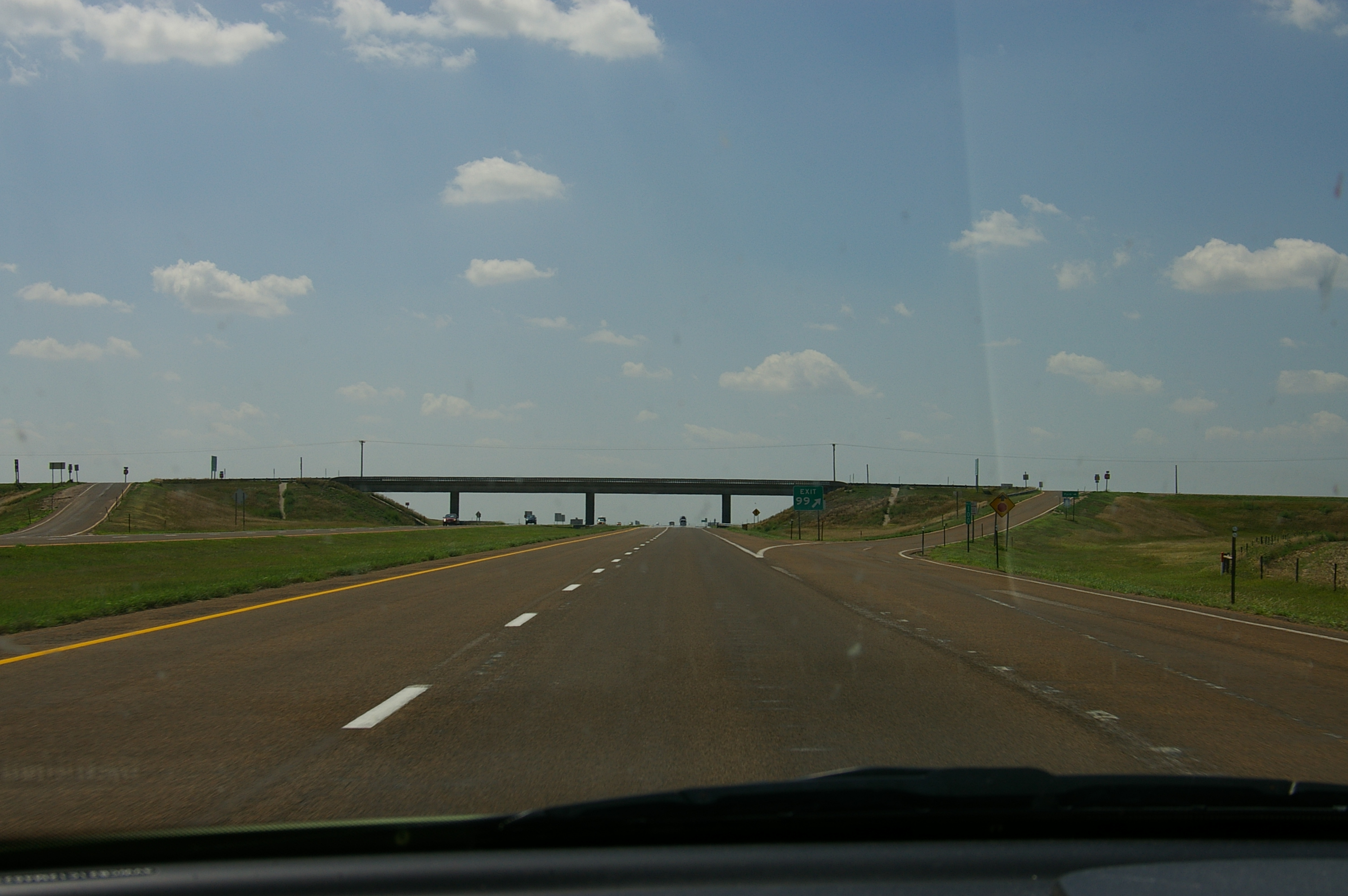 Driver's view of road overpass crossing a stretch of rural interstate highway
