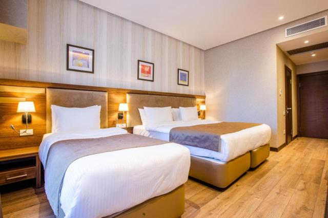 A bed or beds in a room at City Park Hotel