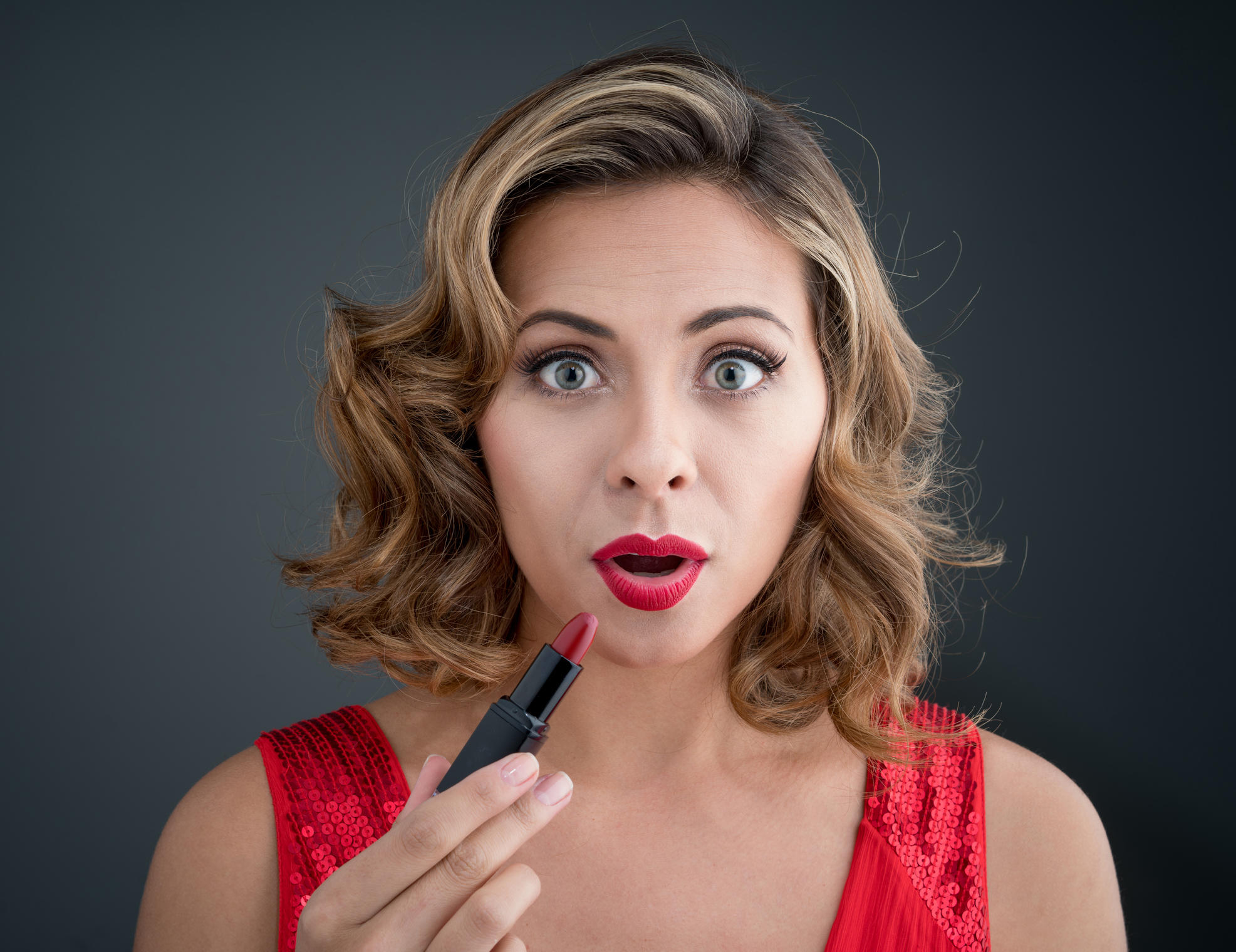 Surprised woman applying red lipstick and wearing beautiful makeup - fashion concepts