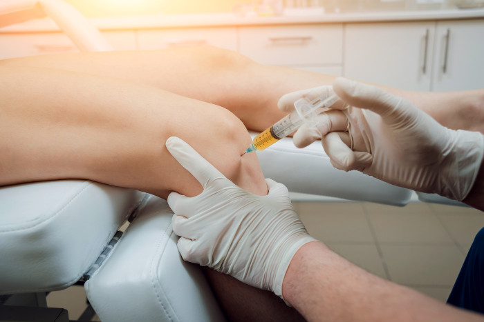 A doctor injecting prp into a patient's knee