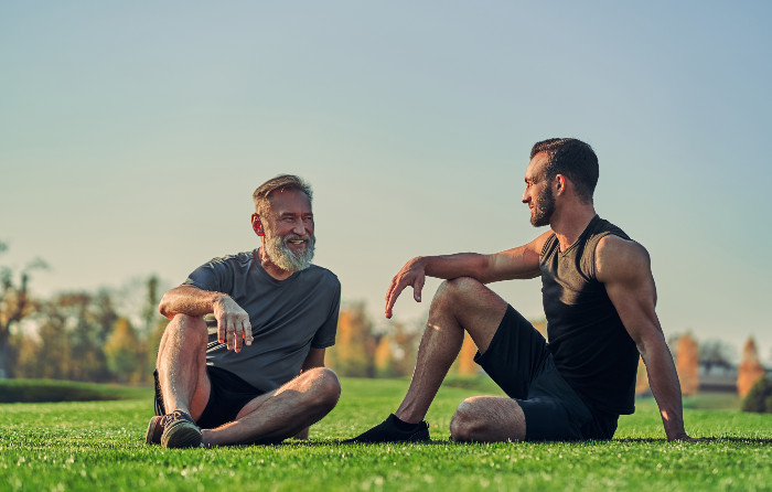 A young and elderly man take a break from exercising