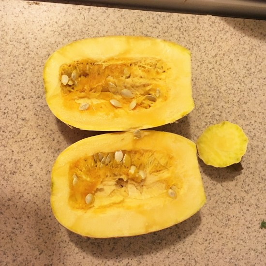 Carefully cut squash in half and scoop out the seeds