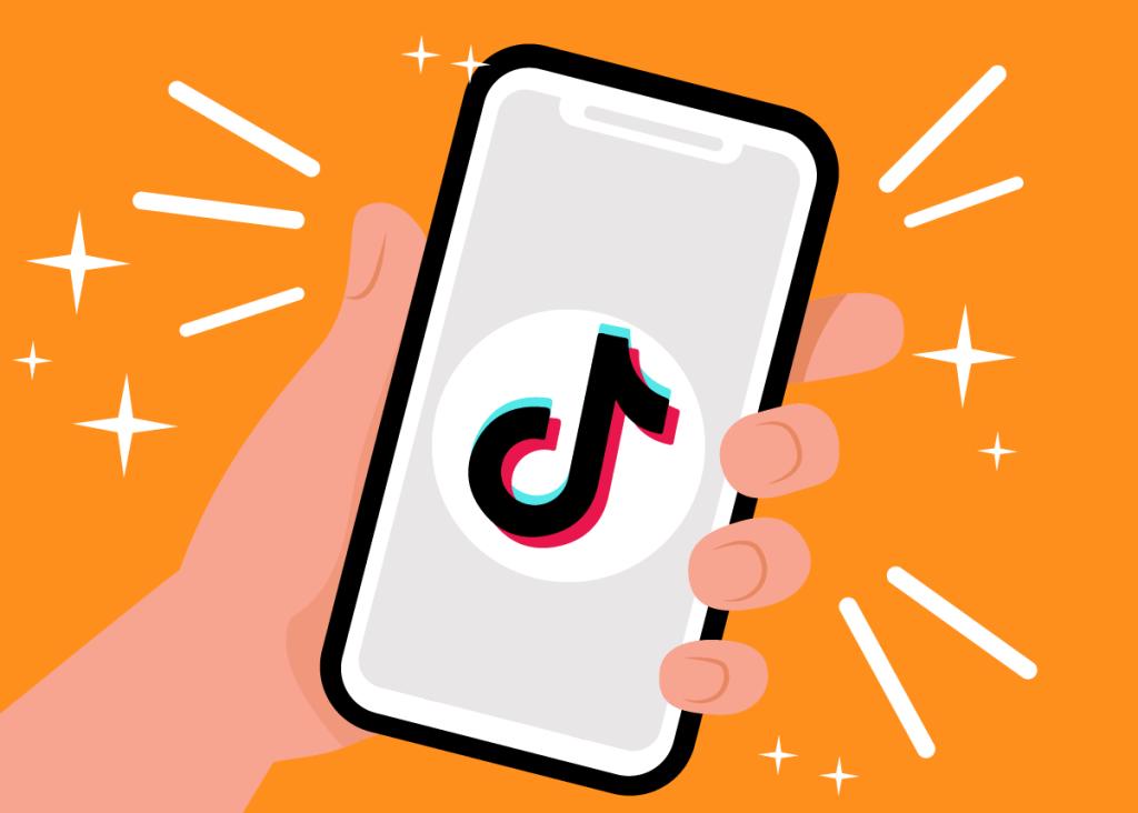 Mão segurando um smartphone com o aplicativo do aberto, transmitindo a ideia de que estratégias de marketing para o TikTok podem ser de fácil acesso