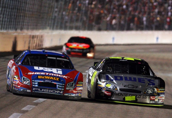 Jimmie Johnson, driver of the #48 Lowes/Kobalt Chevrolet, races Matt Kenseth, driver of the #17 USG Ford, side by side as they pass Juan Pablo Montoya, driver of the #42 Texaco/Havoline Dodge, during the NASCAR Nextel Cup Series Dickies 500 at Texas Motor Speedway on November 4, 2007 in Fort Worth, Texas. (Photo by Jamie Squire/Getty Images)