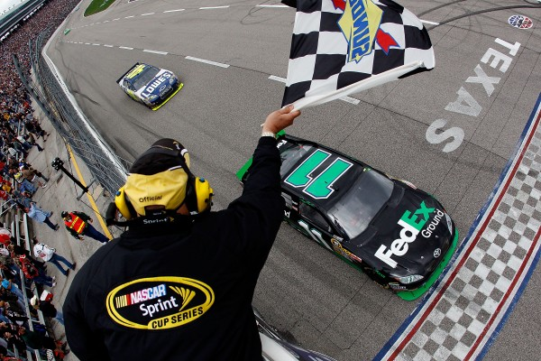 Denny Hamlin, driver of the #11 FedEx Ground Toyota, crosses the start/finish line to take the checkered flag and win the NASCAR Sprint Cup Series Samsung Mobile 500 at Texas Motor Speedway on April 19, 2010 in Fort Worth, Texas. (Photo by Chris Graythen/Getty Images)